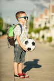 Caucasian little boy standing on the road and holding his soccer Royalty Free Stock Images