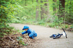 Caucasian little boy toddler in blue jacket, jeans and baseball cap with bike in park playground outside, sitting on ground Stock Photography