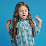 Caucasian little girl on a blue background. White caucasian little girl on a blue background stretches Stock Images