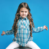 Caucasian little girl on a blue background. White caucasian little girl on a blue background stretches Royalty Free Stock Photo