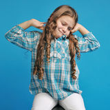 Caucasian little girl on a blue background. White caucasian little girl on a blue background stretches Stock Photo