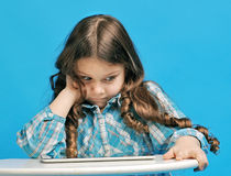Caucasian little girl on a blue background. White little girl is surprised with the tablet Royalty Free Stock Photos