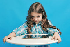Caucasian little girl on a blue background. White little girl is surprised with the tablet Stock Photography