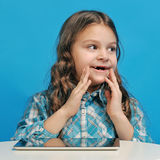 Caucasian little girl on a blue background. White little girl is surprised with the tablet Stock Photo