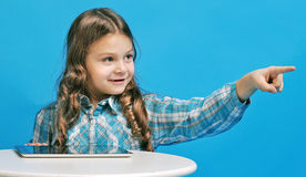 Caucasian little girl on a blue background. White little girl is surprised with the tablet Stock Photos
