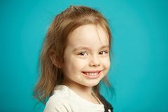Caucasian little girl cute smiling, close-up portrait of beautiful child on blue isolated background. royalty free stock photography