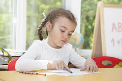 Caucasian little girl drawing with pencils Royalty Free Stock Image