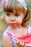 Caucasian little girl eats a slice of watermelon Stock Image
