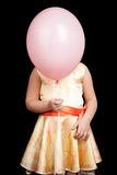 Caucasian little girl hides her face under balloon Royalty Free Stock Image