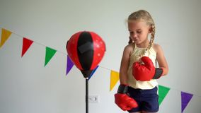 Caucasian little girl hitting boxing pear wit boxing gloves. slow motion