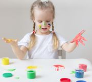 Caucasian Little Girl Painting with Colorful Hands Paints at Home Early Education. Preparing for School Preschool Development Children Game stock photo