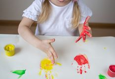 Caucasian Little Girl Painting with Colorful Hands Paints at Home Early Education. Preparing for School Preschool Development Children Game stock photography
