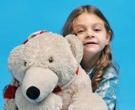 Caucasian little girl with a polar bear. White caucasian little girl with a polar bear on a blue background Royalty Free Stock Photos