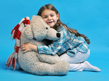 Caucasian little girl with a polar bear. White caucasian little girl with a polar bear on a blue background Stock Photography