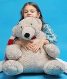 Caucasian little girl with a polar bear. White caucasian little girl with a polar bear on a blue background Stock Photo
