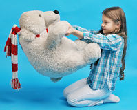Caucasian little girl with a polar bear. White caucasian little girl with a polar bear on a blue background Stock Images