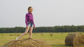 Caucasian little girl stand on haystack sunny day. Blond cute child posing on dry hay panning shot. Happy smiling kid on stack of yellow straw. Joyful beauty stock footage