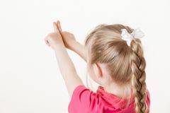 Caucasian little girl turning back and indicating something up Royalty Free Stock Photography