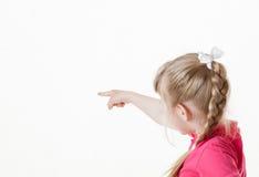 Caucasian little girl turning back and indicating something Royalty Free Stock Photography