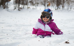 Caucasian little girl in winter clothes playing in the snow Royalty Free Stock Photo