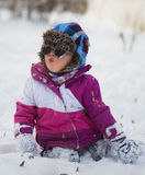 Caucasian little girl in winter clothes and sunglasses playing in the snow Royalty Free Stock Photo