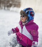Caucasian little girl in winter clothes and sunglasses playing in the snow Stock Images
