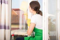 Caucasian lokalvårdkvinna som tvättar fönstret fotografering för bildbyråer