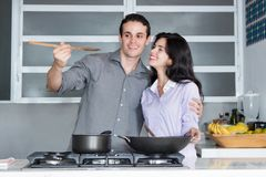 Caucasian love couple cooking at kitchen Royalty Free Stock Photos