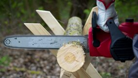 Lumberjack in gloves saws firewood on sawhorses with a electric saw in forest