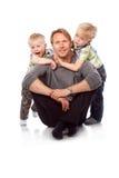Caucasian lycklig fader med två barn som sitter på golvet Royaltyfri Foto