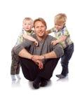 Caucasian lycklig fader med två barn som sitter på golvet Arkivfoton