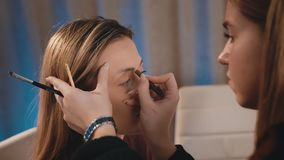 Caucasian make-up artist draws and induces the shape of the eyebrows with a pencil on the face of a Caucasian blonde stock footage