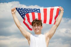 Caucasian male on a beach holding an American flag stock image