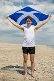 Caucasian male on a beach holding a Scottish flag royalty free stock photo