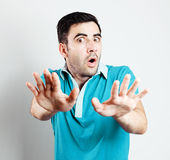 Caucasian male with blue shirt being scared in front of camera Stock Images