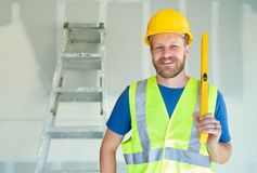 Caucasian Male Contractor With Hard Hat, Level and Safety Vest At Construction Site.  royalty free stock images