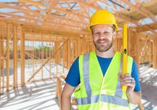 Caucasian Male Contractor With Hard Hat, Level and Safety Vest At Construction Site.  royalty free stock photo