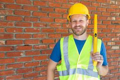 Caucasian Male Contractor With Hard Hat, Level and Safety Vest At Construction Site. Caucasian Male Contractor With Hard Hat, Level and Safety Vest At a stock images