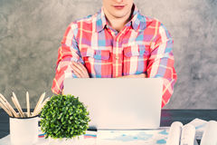 Caucasian male crossed arms. Caucasian male with crossed arms sitting at office desk with plant and other items looking at a laptop screen Stock Images
