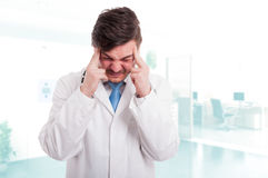 Caucasian male doctor with headache looking exhausted Royalty Free Stock Images