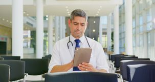 Caucasian male doctor holding digital tablet in the lobby at office 4k stock footage