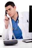 Caucasian male doctor sitting at the desk Royalty Free Stock Images