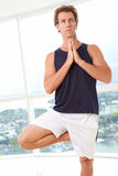 Caucasian male doing yoga tree pose. Indoors in high  rise apartment Stock Photo