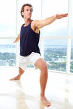 Caucasian male doing yoga warrior pose Royalty Free Stock Photos