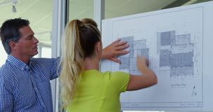 Caucasian male and female architects discussing over blueprint in the office 4k stock footage