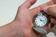 Caucasian male hand adjusting the pocket watch. Conceptual image of daylight savings time Royalty Free Stock Photography