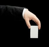 Caucasian male hand in a business suit isolated. Caucasian male hand in a business suit, holding the white empty business card, low-key lighting composition Royalty Free Stock Photos