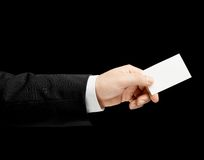 Caucasian male hand in a business suit isolated. Caucasian male hand in a business suit, holding the white empty business card, low-key lighting composition Stock Photos
