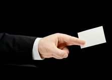 Caucasian male hand in a business suit isolated. Caucasian male hand in a business suit, holding the white empty business card, low-key lighting composition Stock Images