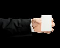 Caucasian male hand in a business suit isolated. Caucasian male hand in a business suit, holding the white empty business card, low-key lighting composition Stock Photo